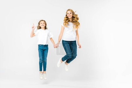 happy mother with adorable daughter jumping on white background