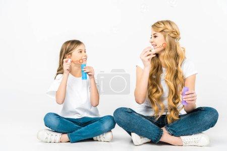 Photo pour Sourire, mère et fille soufflant des bulles de savon tout en étant assis sur le sol avec les jambes croisées sur fond blanc - image libre de droit
