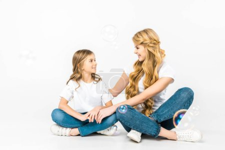 Photo for Smiling mom and daughter sitting on floor with crossed legs and looking at each other while soap bubbles flying around on white background - Royalty Free Image