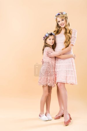 Photo pour Une fille adorable et belle maman élégante dentelle robes et couronnes florales étreindre et regardant les uns les autres sur fond jaune - image libre de droit