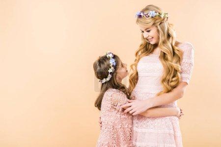 Photo pour Mère et fille dans belles robes et couronnes de fleurs embrassant et en regardant les uns les autres sur fond jaune - image libre de droit