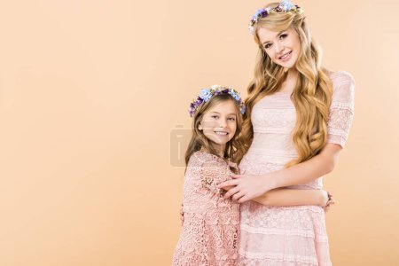 Photo for Adorable daughter and beautiful mom in elegant lace dresses and colorful floral wreaths hugging while looking at camera on yellow background - Royalty Free Image