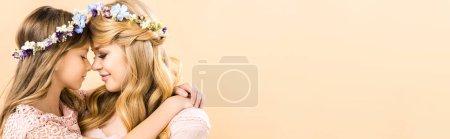 Photo pour Belle femme et enfant adorable en couronnes florales colorés, étreindre face à face avec les yeux fermés sur fond jaune, espace copie - image libre de droit