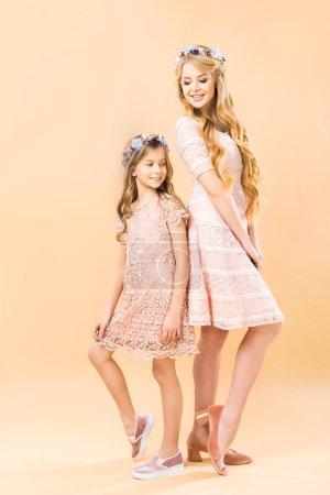 Photo pour Mère et fille élégantes dentelles robes et couronnes florales debout dos à dos et posant à la caméra sur fond jaune - image libre de droit