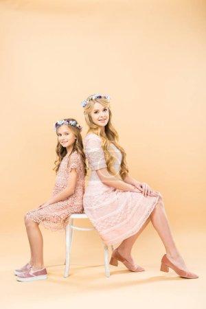 Photo pour Heureuse mère et fille en délicates dentelles robes et couronnes florales assis sur la même chaise et regarder la caméra sur fond jaune - image libre de droit