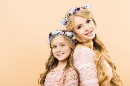 Photo for Beautiful woman and cute daughter in colorful floral wreaths standing back to back and looking at camera on yellow background - Royalty Free Image