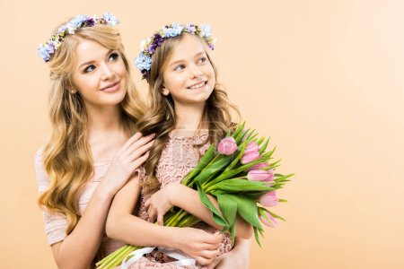 Photo for Beautiful mother and adorable daughter in floral wreaths looking away and smiling on yellow background - Royalty Free Image