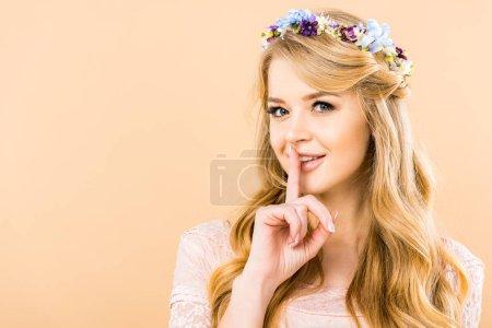 Photo pour Belle femme dans une gerbe de fleurs montrant hush signe sur fond jaune - image libre de droit