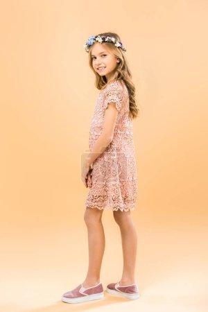Photo pour Mignon enfant souriant en belle dentelle robe et couronne florale, regardant la caméra sur fond jaune - image libre de droit