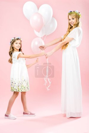 Foto de Beautiful mother and cute daughter in white elegant dresses and floral wreaths holding festive air balloons on pink background - Imagen libre de derechos