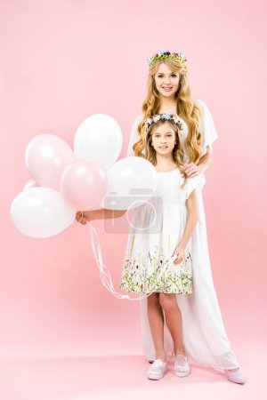 Photo for Adorable daughter holding festive air balloons while standing near beautiful mother on pink background - Royalty Free Image