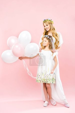 Photo pour Cute child holding festive air balloons while standing near smiling mother on pink background - image libre de droit