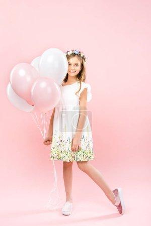 Foto de Adorable child in elegant white dress and floral wreath holding festive air balloons on pink background - Imagen libre de derechos