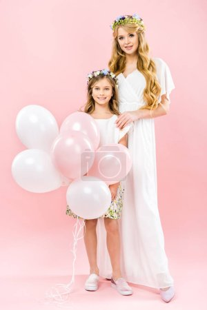 Photo pour Cute smiling child with festive air balloons standing near beautiful mother on pink background - image libre de droit