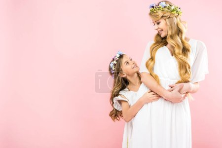 Photo for Beautiful mother and adorable daughter in elegant white dresses and colorful floral wreaths on pink background with copy space - Royalty Free Image
