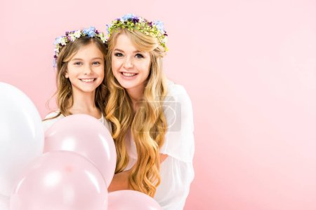 Foto de Happy mother and daughter in colorful floral wreaths holding festive air balloons on pink background - Imagen libre de derechos