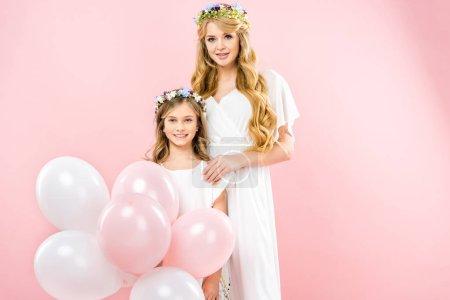 Foto de Cute smiling child with festive air balloons standing near beautiful mother on pink background - Imagen libre de derechos