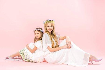 Photo pour Jolie femme et une fille cute dans d'élégantes robes blanches et couronnes florales assis dos à dos sur le sol et regardant la caméra sur fond rose - image libre de droit