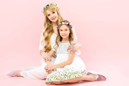 Foto de Beautiful woman and adorable daughter in elegant white dresses and floral wreaths sitting on floor and looking at camera on pink background - Imagen libre de derechos