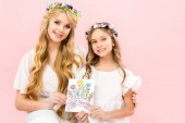 smiling mother and cute child in delicate white dresses and floral wreaths holding happy mothers day greeting card on pink background