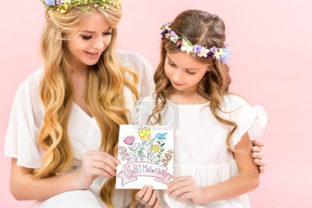 Photo pour Beautiful mother and adorable daughter in white elegant dresses and floral wreaths holding happy mothers day greeting card on pink background - image libre de droit
