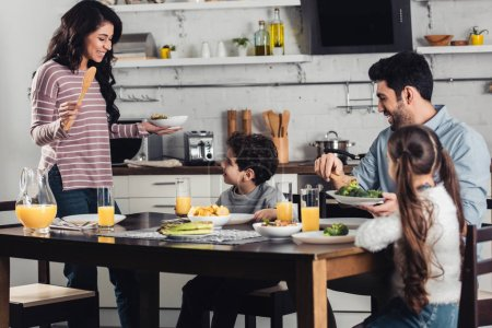 attractive latin woman looking at son while holding plate near daughter and husband during lunch