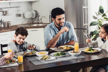 handsome latin father looking at daughter while having lunch near wife and son