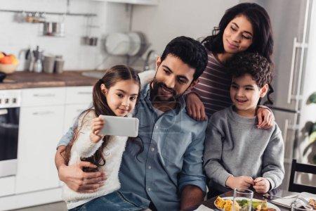 cheerful latin kid taking selfie with hispanic family at home