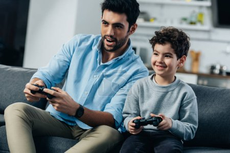 happy latin father and son playing video game at home