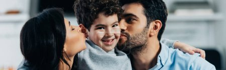happy latin father and mother kissing cheeks of adorable son at home