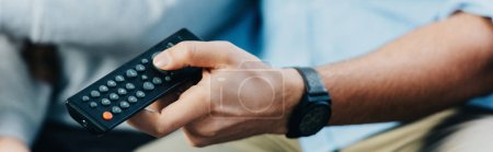 Photo pour Vue recadrée de l'homme tenant la télécommande à la main - image libre de droit
