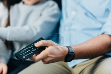 Photo pour Vue recadrée de l'homme tenant la télécommande dans la main près des enfants - image libre de droit