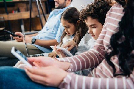 Photo pour Foyer sélectif des enfants utilisant des gadgets près du père et de la mère à la maison - image libre de droit
