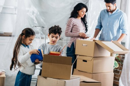 selective focus of cute kids holding books while parents standing near boxes in new home