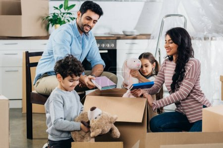 Photo for Happy latin family unpacking boxes in new home - Royalty Free Image
