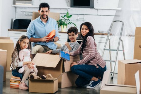 Photo for Cheerful hispanic family unpacking boxes in new home - Royalty Free Image