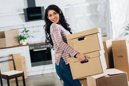 Photo pour Femme latine joyeuse maintenant et boîtes en se déplaçant dans la nouvelle maison - image libre de droit
