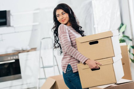 Photo for Happy latin woman holding boxes while moving in new home - Royalty Free Image