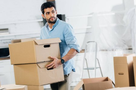 Photo for Handsome latin man holding boxes while moving in new home - Royalty Free Image