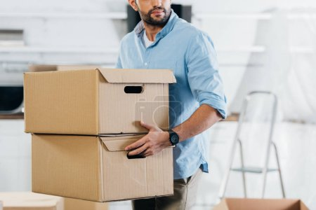 Photo for Cropped view of man holding boxes while moving in new home - Royalty Free Image