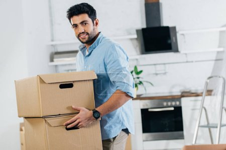 Photo for Cheerful latin man holding boxes while moving in new home - Royalty Free Image