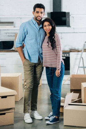 Photo for Cheerful latin couple standing and smiling near boxes in new home - Royalty Free Image