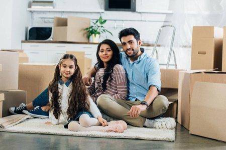 glückliches lateinisches Ehepaar sitzt im Teppich neben Tochter im neuen Zuhause