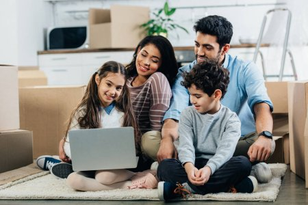 cheerful hispanic family looking at laptop while sitting on carpet in new home
