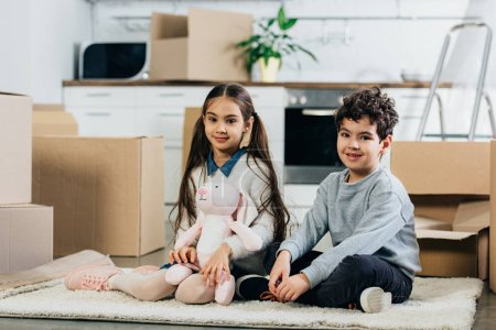 Photo for Happy children sitting on carpet with soft toy near boxes while moving in new home - Royalty Free Image