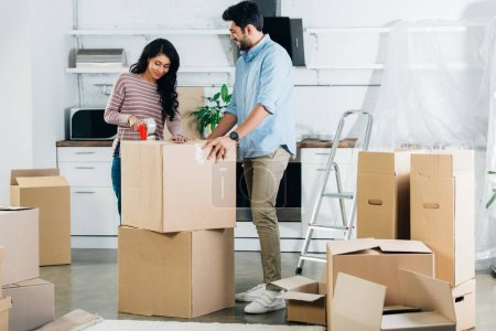 Photo for Cheerful latin couple packing boxes while moving to new home - Royalty Free Image