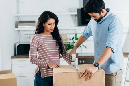 Photo for Happy latin couple packing boxes while moving to new home - Royalty Free Image