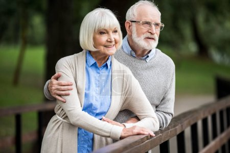 selective focus of senior husband hugging smiling wife while standing together by wooden bridge railing