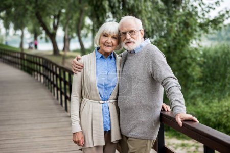 Photo for Selective focus of happy senior couple hugging while standing on wooden bridge in park - Royalty Free Image
