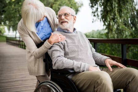 senior woman looking at smiling husband in wheelchair while holding hand on his shoulder